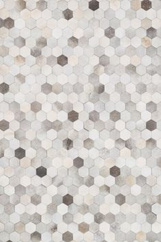 This hand stitched, graphic rug is a one-of-a-kind, contemporary twist on cowhide. Shades of grey, ivory and beige hide are arranged in a hexagon pattern.