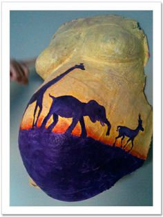 During both pregnancies, my sister Emma had her baby bump set in a belly cast as a memento. Hannah painted a scene of an African savanna on . Baby Belly Cake, Pregnant Belly Cast, Belly Cast Decorating, Belly Art, Belly Casting, Lion King Baby, Future Boy, Safari Theme, Baby Time