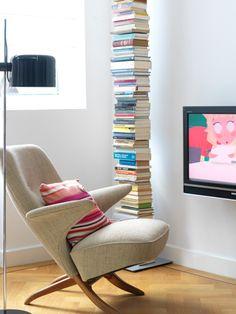 In deze televisiekamer annex leeshoek is een decoratieve boekenzuil bij elkaar gestapeld.