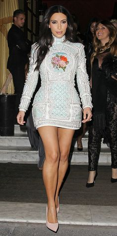 Kim Kardashian was dressed to impress on her pre-wedding night on the town, showing off her legs in a high-neck exquisitely embellished aqua Balmain mini and elongating them even further with nude pumps.