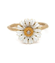 """The Daisy was known as the """"day's eye"""" in the time of Chaucer, for it would face the sun in the morning and close in the evening. It's classic shape and form and seemingly wide-eyed beauty is still regarded as a symbol of innocence and lack of pretentiousness. Our 14K matte gold signature twig band is accented an original art nouveau enamel daisy, set with an old cut diamond center (0.03 ct) We like to think of this petite diamond daisy ring as a reminder to appreciate the simple things in…"""