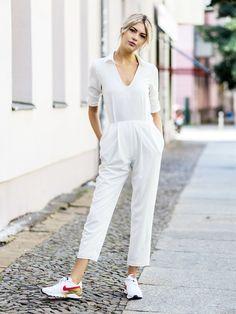 Bloggerin Ebba im stylischen weißen Jumpsuit mit sportlichen Sneakern.
