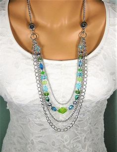 Long Blue and Green Beaded Multi Strand Silver Chain Necklace, handmade by Ralston Originals. This beaded necklace has blue, green, silver and clear beads in glass, crystal and acrylic. The 3 multi strands of silver metal chain are different sizes and shapes. The multi strands of