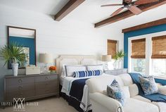 master Beautifully designed tropical blue and gray bedroom boasts a two tone tan and white leather headboard positioned flush against a white shiplap wall behind a bed dressed in a white and navy blue duvet with navy blue border shams located behind a long blue striped bolster pillow.
