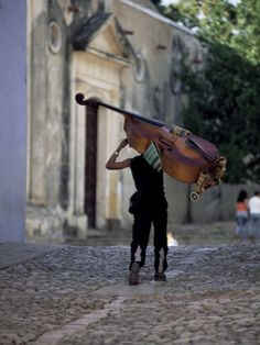 Musician Carrying Double Bass Along Cobbled Street to Plaza Mayor, Trinidad, Cuba Photographic Print by Lee Frost at Art.com