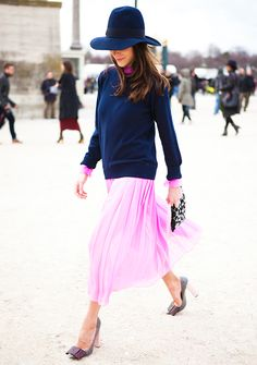 Navy crew neck sweater worn over a pink pleated midi skirt