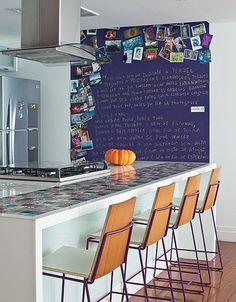 A cozinha deste apartamento, projetado peça arquiteta Laura Faria, tem chapa metálica pintada de roxo. Lá, a moradora exibe cartões-postais, fotos de viagens e obras de arte, além de textos de escritores consagrados e de sua própria autoria