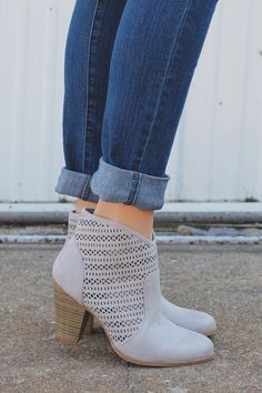 Our Tailgates & Tanlines Bootie is a pair of almond toe dove grey booties with perforated sides, side zipper and stacked wooden heel.