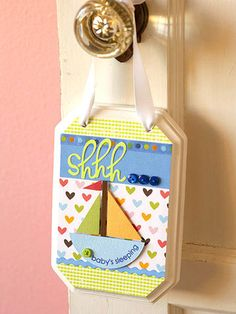 "Wooden Plaque. Amy prepped an unfinished wooden plaque by spray-painting it white and drilling two holes at the top for a ribbon. She completed the background using patterned paper, ribbon, and paper trim ""waves,"" then added a paper-pieced sailboat. Buttons and stickers complete the look."
