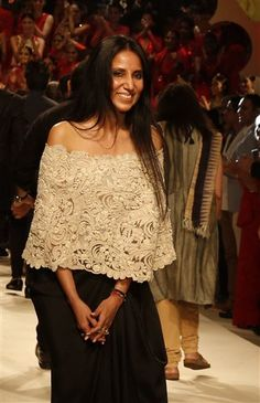 In this Sunday, March 29, 2015 photo, Indian designer Anamika Khanna smiles as she walks the runway at the grand finale of Amazon India Fashion Week in New Delhi, India. (AP Photo/Manish Swarup)