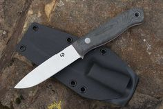 This knife began as an exploration into how to create a custom handmade version of the ever popular and practical Mora Knife (in the Puukkostyle). I solicited customers and buschraftusers on what they would want if they could improve on this design. My Bushcraft knife is the result of that process. The most significant improvement was the addition of a small but noticeable guard that still allowed the edge to come right up to the handle. Another improvement was a full tang handle with pins…