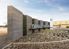 Chandler Viridian's primary identification sign is over 82' long. Push through illuminated channel letters mounted to board form concrete and glass rock gabion baskets brand the cornerstone.