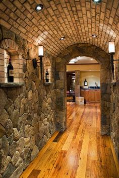 Custom Stone (NE Fieldstone) entrance hallway with barrel ceiling (brick). Niche bottle displays, custom lighting, & antique chestnut flooring....