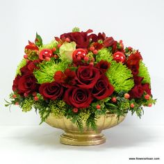 A Christmas floral arrangement of roses,hypericum,skimmia,and greenery with red ornaments in a golden bowl.