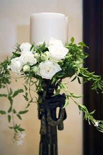 White roses and lush leaves surround white candles on a metal pedestal.