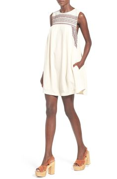 Earth-toned embroidery embellishes the yoke of this white swing dress with a breezy silhouette.