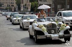 A #Lebanese bride carries an umbrella while sitting in an old Car accompanied by a wedding convoy along a street in #Beirut #WeAreLebanon