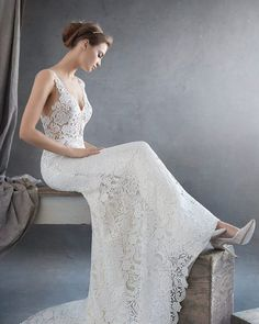 Sheath wedding dress in Venise lace with 'V' neckline and lace straps. Features low back to waist, sheer hand-appliqued lace bodice, and narrow falling skirt with sheer panels at sides and chapel train.