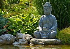 statue de jardin zen - Bouddha en pierre de lave, bassin d'eau avec plantes aquatiques et pierre naturelle