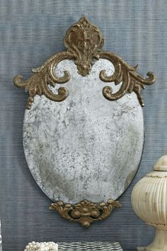 Celia Mirror Gaze into this aristocratic smoked mirror with its hand-carved iron embellishments at top and bottom. It has the distressed look and feel of an antique salvaged f