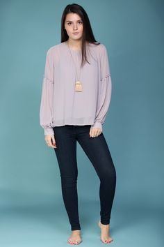 A basic updated with subtle sleeve details and gorgeous color. The perfect blouse for work or a night out.