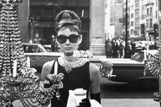 """Audrey Hepburn steht im Film """"Frückstück bei Tiffanys"""" mit einer Sonnenbrille vor einem Schaufenster (1961)"""