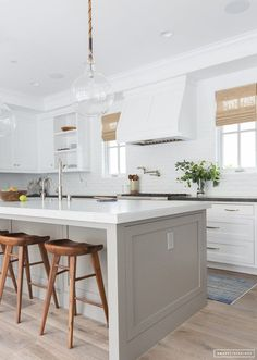 two tone shaker cabinets, greige island, white cabinetry, white stone counters, glass orb pendants, rustic wood floors, rustic wood stools, white brick backsplash, rectangular hardware