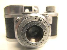 RUBIX 16 Manufacturer : Sugaya Koki ,Sugaya Optical Co Ltd Japan. Date's : 1950s Lens : Hope Anastigmat  f3,5/25mm . Shutter : B ,1/25-1/150sec . Subminiature takes 50 exposures 10x14mm on 16 mm cassette or 17,5mm paper backed rollfilm