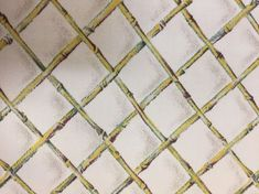 A bamboo lattice fabric in a green, brown, yellow, and white color palette.