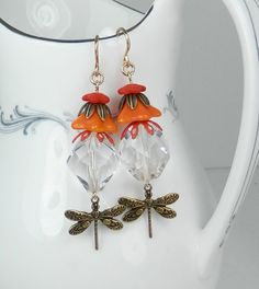 Premium Czech glass flower beads in shades of coral orange layer with leaf embossed and vintage enamel bead caps and faceted glass crystal. Below dangles antiqued brass dragonflies. All other metal including high quality sturdy ear wires is gold filled. Overall length of earrings is 2 1/4 inches or 5.8 centimeters.  All items are giftboxed and ready for giving.  What is gold filled? Gold Filled products have approximately 100 times more gold than gold plated products. Gold filled looks a...