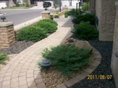 A manufactured brick walkway leading from the front of the house around to the backyard with nice gentle curves. Lighting is added for safety along the edge of the xeriscaped gravel beds. Picture permission of a Neighbourhood Dream Yard Homeowner.
