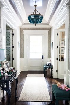 """""""The gray- lacquered ceiling and dark aqua chandelier work so well together,"""" she says. Two blue ottomans not only play up the overall color scheme, but provide the perfect place for slipping on shoes before heading outside. And a plush runner provides a warm welcome for guests."""