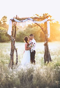 Brides.com: 75 Amazing Ceremony Structures A whimsical, forest-inspired wedding arbor constructed of natural tree branches and sprinkled with wildflowers.Photo: Leighanne Herr