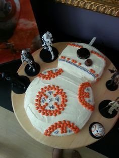 Easy Star Wars BB-8 Cake Made with Reeses Pieces, Editable Silver Decorative Orbs, Rolo, Oreo, and a White Chocolate covered Pretzel Stick