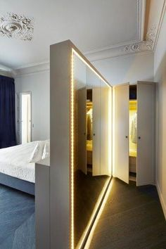 Great idea to create a sort of walk-in closet behind the bed. Great lights and mirror.