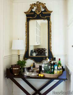 In a niche adjacent to the study, a small bar is set up on a tray table Scheerer had made in India. The vintage mirror is a thrift-shop find.