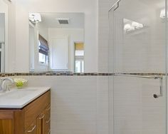 narrow accent band emerges from shower, continues as top of wainscoting and backsplash. Houzz.com