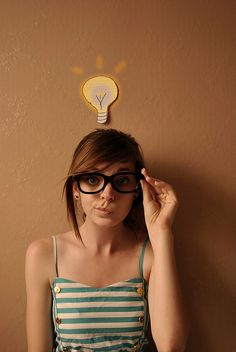 Nerdy girl with glasses and green stripy dress with lightbulb idea