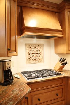 Wood Hoods- Stainless steel appliances, table style seating at counter height, recessed corner cooktop with wall ovens, custom wood hood, custom tile backsplash, birch cabinets with granite countertops
