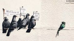 """A mural by Banksy satirizing racism is erased after a complaint that the painting itself was """"offensive and racist. The artwork was painted in the British town of Clacton-on-Sea where the anti-immigrant U.K. Independence Party hopes to win its first Parliament seat. The mural showed a group of pigeons holding signs reading """"Migrants not welcome,"""" and """"Go back to Africa"""" directed at a small, more exotic green bird that appears to be cowering at some distance on the same wire."""