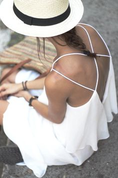Perfect summer outfit: a flowy white dress with crossed straps on the back and a simple panama straw hat!
