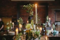 White flower centrepieces in mismatched bottles | Photography by http://jesspetrie.com/