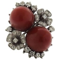 An 18k white gold ring set with coral (12mm x 13mm) and approximately 0.75ctw of H/VS diamonds. DESIGNER: Not Signed MATERIAL: 18k Gold GEMSTONE: Coral, Diamond DIMENSIONS: Ring Size 7.5, Top of Ring