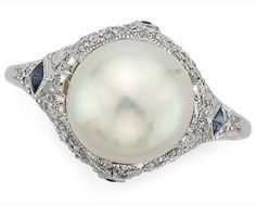 Platinum, Natural Pearl, Diamond and Sapphire Ring  Platinum, centering one pearl* approximately 9.3 mm., the pierced mount accented by 4 diamond-shaped cabochon sapphires, set with numerous small old European-cut diamonds, circa 1915.