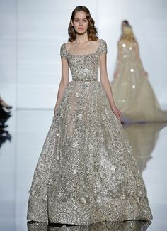 Long sleeved dress featuring a full skirt and draped waist in bronze silk tulle and crystal dot detailing