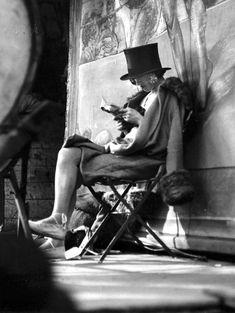 André Kertész, Carnival, Paris (woman reading behind stage), 1926