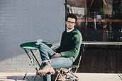 A stylish young man sitting on the patio at a coffee shop looking at camera whie checking his phone