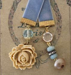 Dusty blue velvet ribbon bookmark with a large creamy rose cabochon, an old pearl button, vintage crystal bauble, old rhinestone spacer and pale blue Peruvian Opal rondelles.  $16