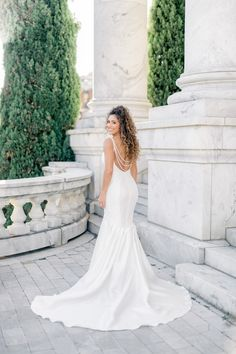Our Tiffany Nicole sexy wedding dress features custom draped sparkle straps along the back, creating the perfect dramatic wedding dress back moment. #weddingdress #wedding #minimalistweddingdress #sexyweddingdress #trumpetweddingdress #bride #bridalgown #customweddingdress #designerweddingdress