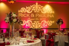 We are LOVING this #gold #gobo #monogram paired with #pink #uplighting!  Such a pretty #wedding #reception. #rentmywedding #diy #weddingplanning #uplight